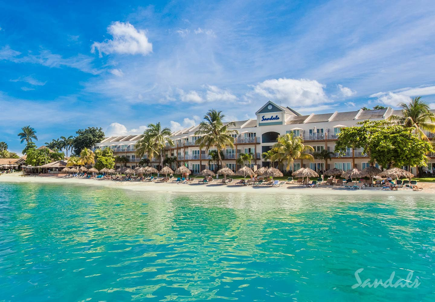 sandy beach with blue ocean water in front of the Sandals Negril beach resort in Jamaica, part of our Sandals vacation deals
