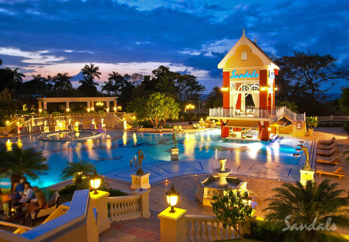 Sandals Ochi Rios resort, Jamaica, light up in the evening, outside swimming pool and dining, showing off the Sandals vacation deals