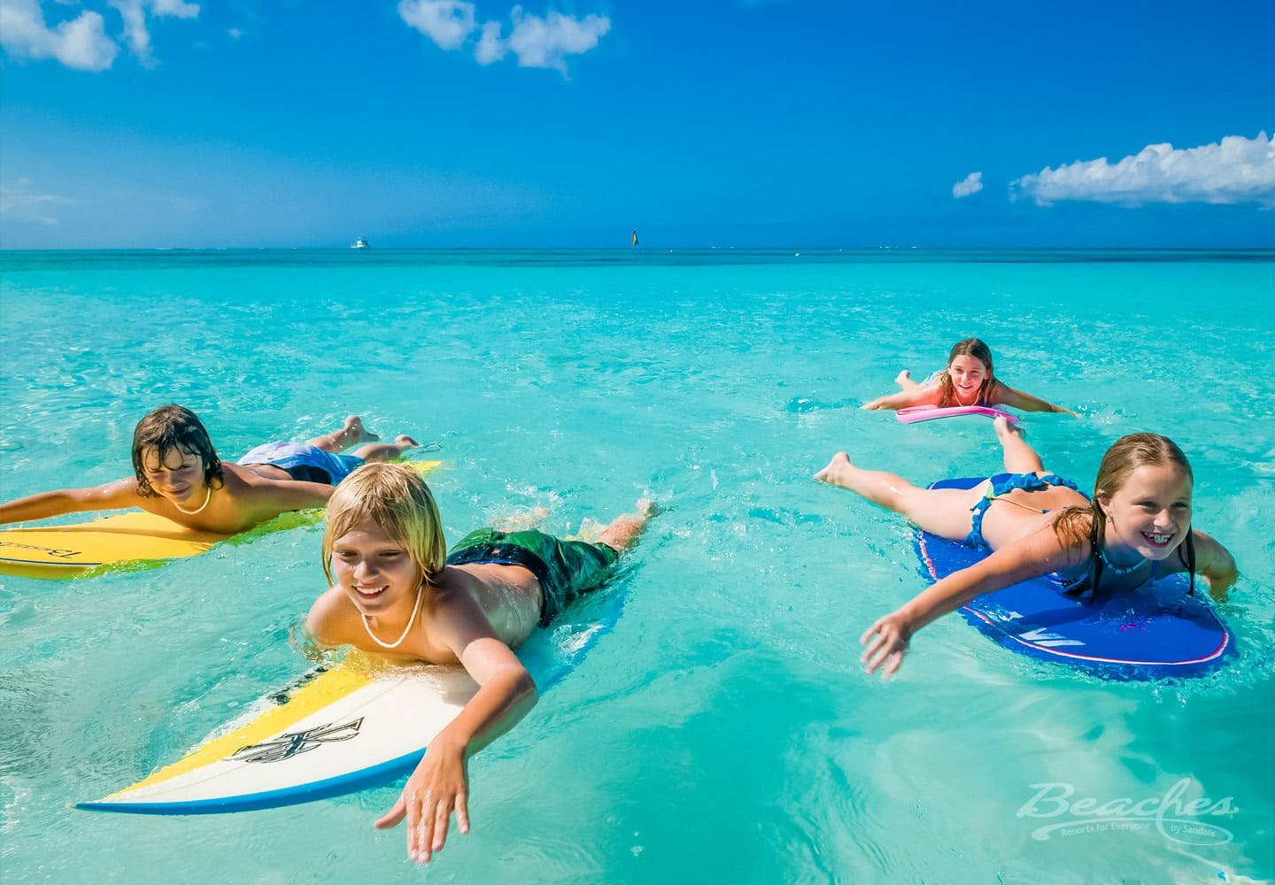 kids paddling in the ocean with their surf boards at a Beaches family resort, all inclusive resorts