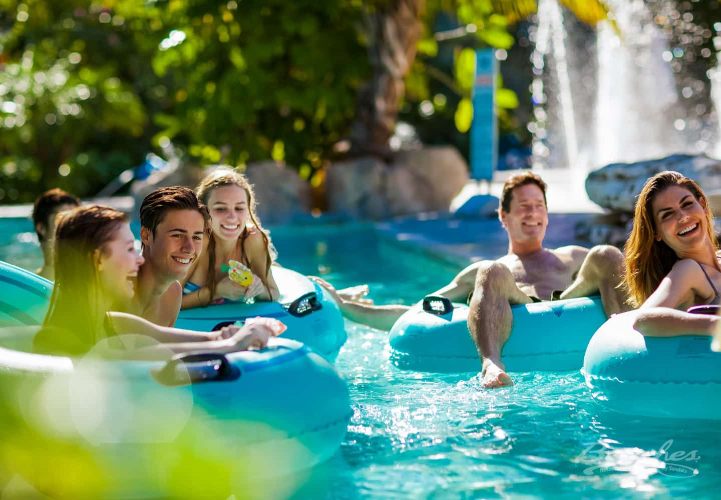 family having fun in the lazy river at the Beaches Turks and Caicos family resort, all inclusive group vacation packages