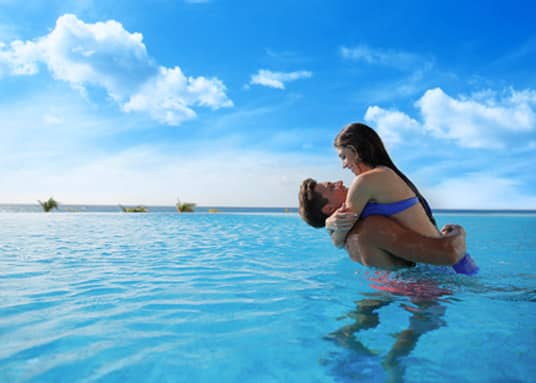 couple having fun together swimming in the ocean at the Le Blanc Spa Resort, one of the Palace resorts in Cancun, Mexico