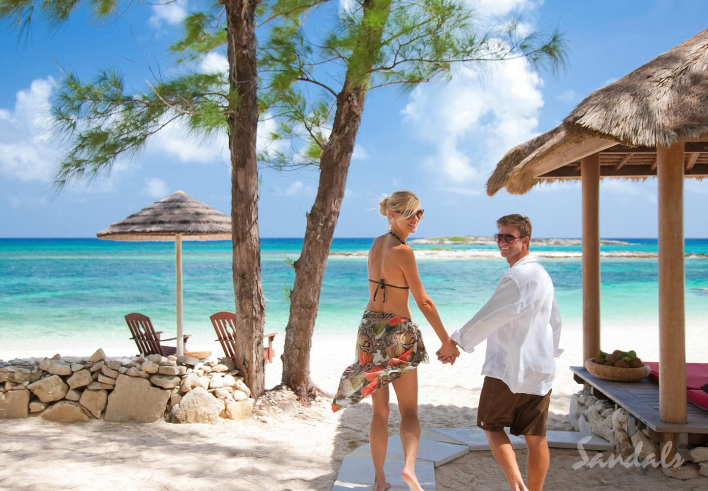 a couple on their honeymoon, holding hands, enjoying their luxury honeymoon vacation at the Sandals Royal Caribbean resort in Jamaica