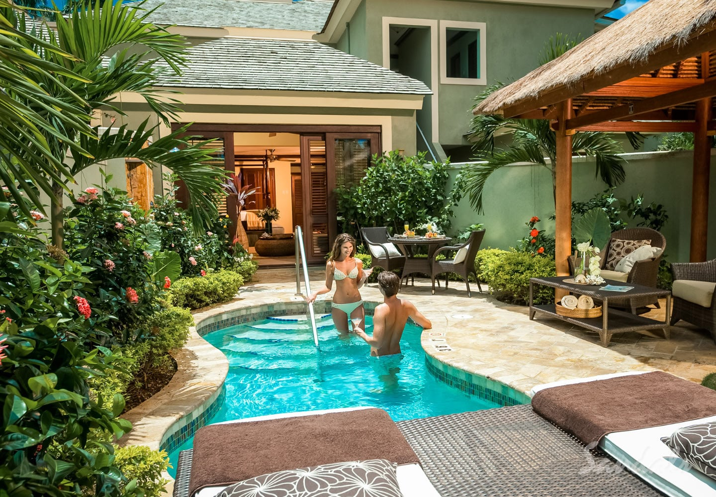 couple in their private pool in front of their private room at the Sandals Negril beach resort in Jamaica, all inclusive adults only vacation packages