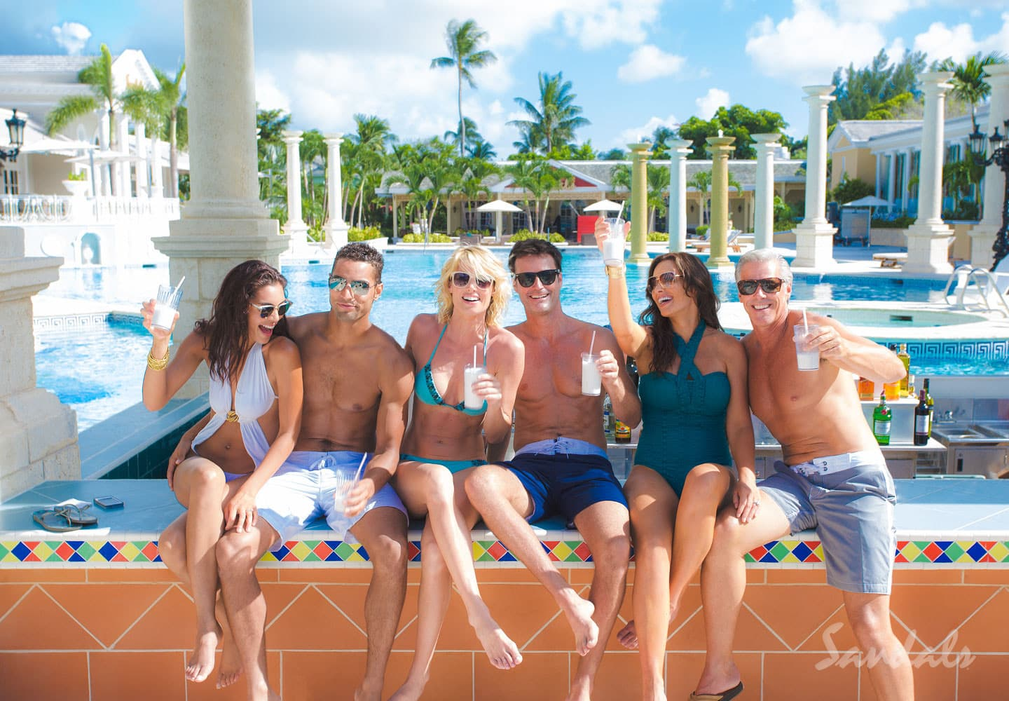 group at a pool bar at the Sandals Royal Bahamian Spa Resort and Offshore Island, Nassau, having fun and drinking cocktails, all inclusive group vacation packages