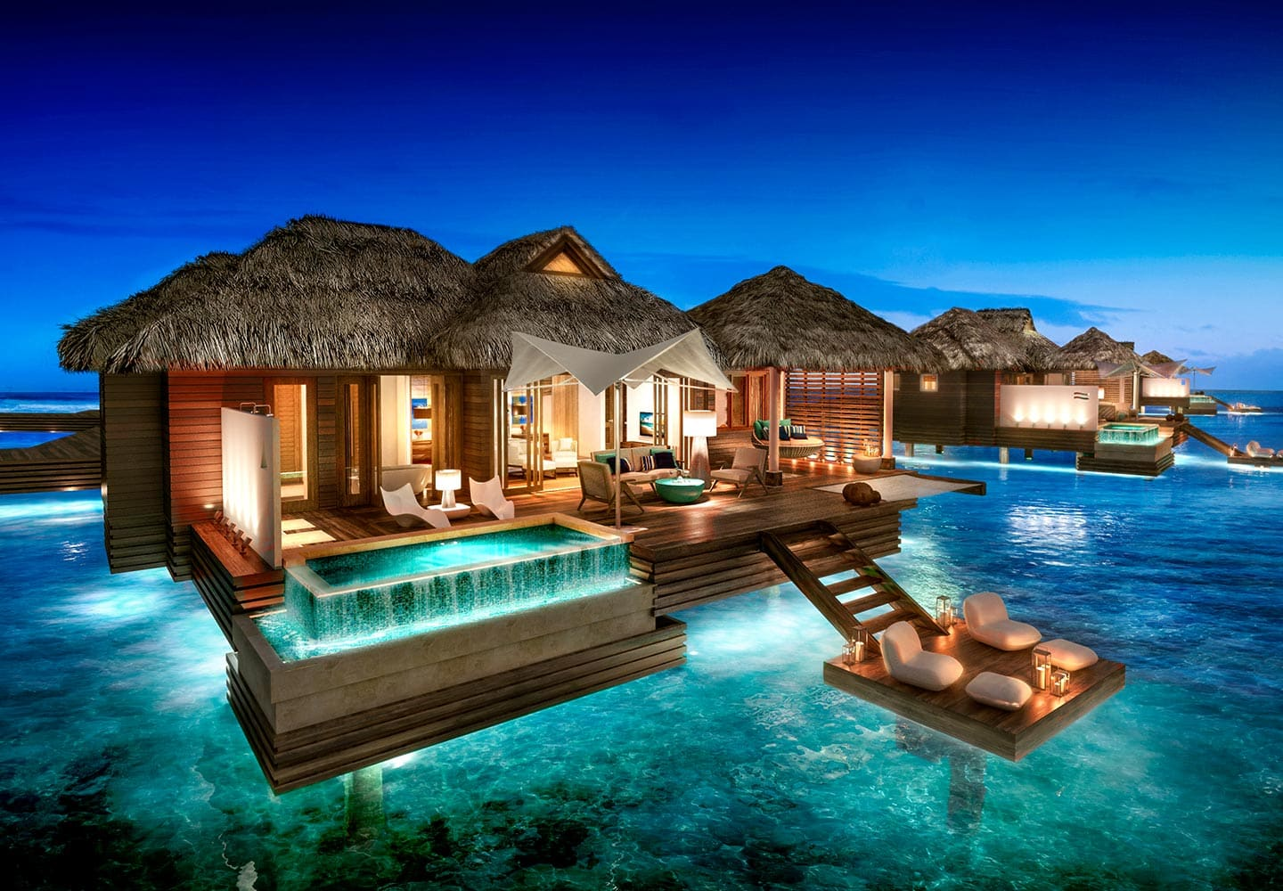 night view of the ultra-luxurious over-the-water bungalows at Sandals Royal Caribbean resort in Jamaica, all inclusive adults only vacation packages