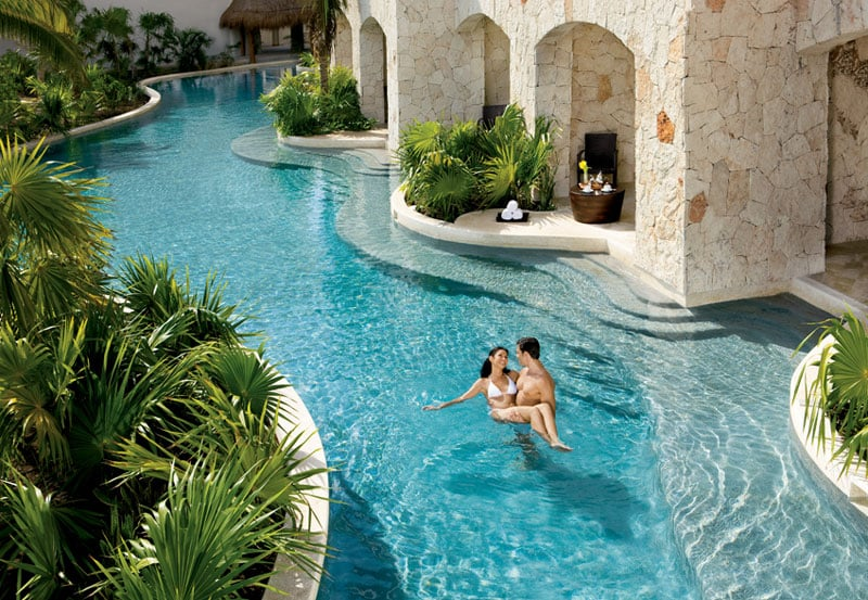 a couple swimming in a private swim-out at one of the luxury Secrets resorts