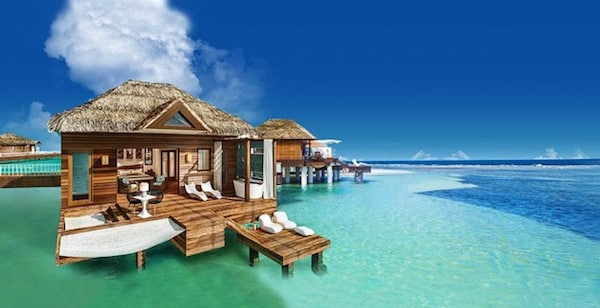 luxury Sandals South Coast over-the-water bungalows, surrounded by blue ocean water and white clouds in the sky in Jamaica