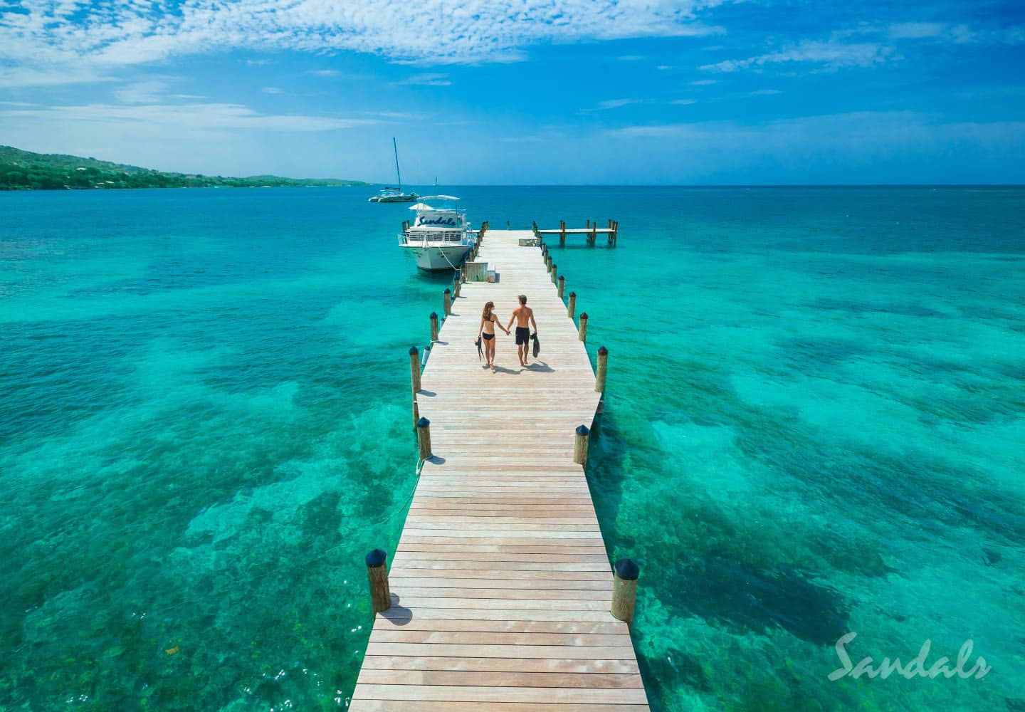 couple walking on the pier at the Sandals South Coast luxury resort in Jamaica, luxury vacations with Southern Travel Agency Augusta, GA