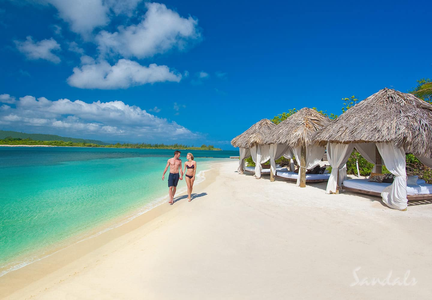 couple walking on the beach of the Sandals Royal Caribbean resort, top 10 most romantic all inclusive resorts offered by Southern Travel Agency Augusta, GA, local travel agency near me