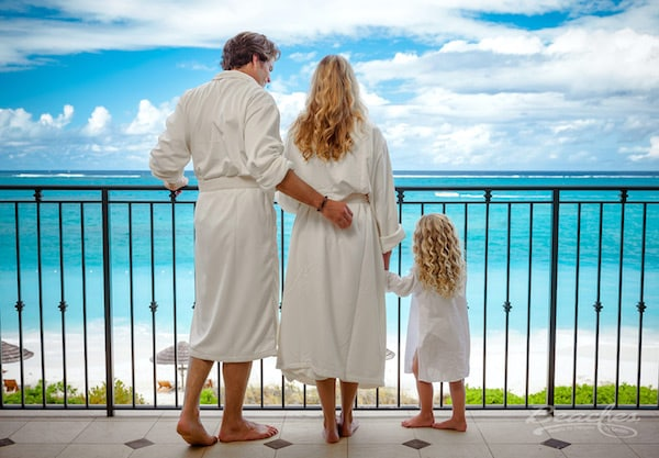 father, mother, and daughter on their private balcony at a Sandals family resort. Family Summer Vacation Ideas beaches turks and caicos resort