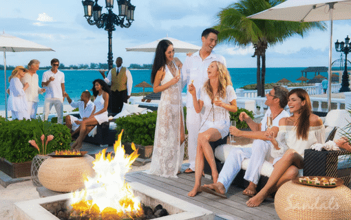 group of people around an outside fire pit, talking, drinking and having a good time at the Sandals Royal Bahamian spa resort in the Bahamas, perfect for all inclusive adult only group vacations, planned by Southern Travel Agency Augusta, GA
