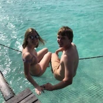 teenagers sitting in a swing over the ocean water at the The One & Only Reethi Rah Maldives Resort Hotel