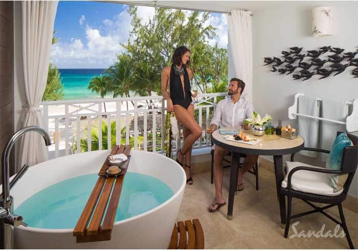 couple in their luxury room with a bathtop in it at the Sandals Barbados luxury resort, part of Southern Travel Agency's all inclusive honeymoon vacations offer